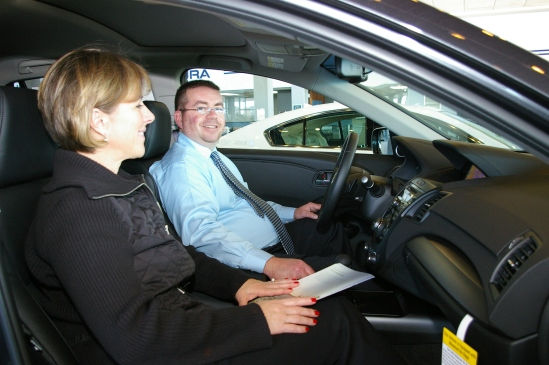 Sales consultants Bronwyn Fitzgerald and Eddie Bittar, with Bloomington Acura Subaru, demonstrate Acura's Bluetooth technology.