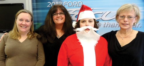 North Country Ford car biller Amy Truchinski, center, put on a Santa suit and collected funds from employees to help four families get on their feet again.  With Snyder is, from left, Controller Lisa Snyder, and Finance and Product Specialists Pam Broman and Patilee Yukl-Dinger-Szymanski.