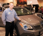 """Dave Harrer feasted on the """"Buick buzz"""" at his first auto show, and polished his people skills. It's his first year in sales after working a factory job. With its signature waterfall grille and portholes, the Buick Encore is a favorite and the first luxury SUV in its class."""