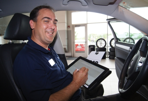 Veteran service advisor Craig Gage performs thorough walk-around inspections with a hand held tablet computer at Westside VW.