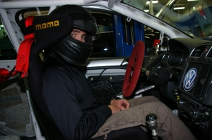 David Daly, in street clothes, inside the new TDI race car, where a Hans device connected to the seat and helmet offer extra protection.