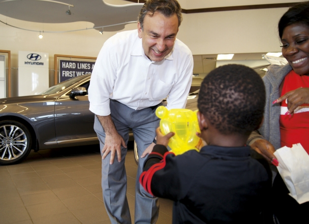 "It's smiles all around as Burnsville Hyundai GM Charlie Rassouli makes animal balloons for customers and their children. He taught himself how when his kids were young. ""Making people happy– that's my life,"" he said."