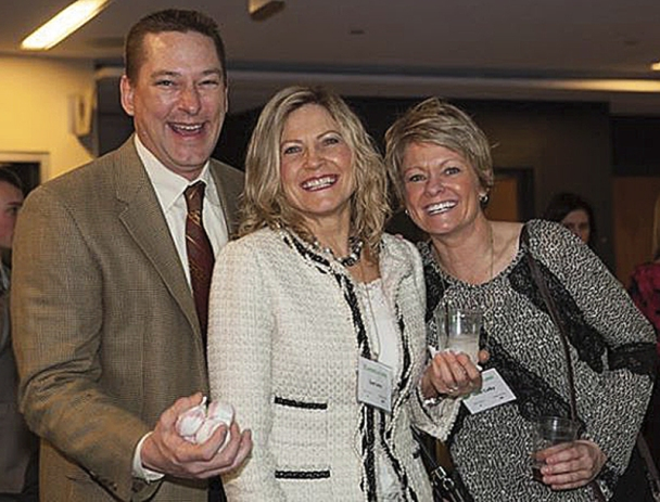 Hopkins Honda sales managers Mike Murphy, left and Heidi Colby, right, celebrate with Sue Lano, new car sales.