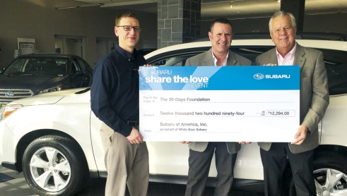 Subaru rep Christian VanFaasen, left and White Bear Acura Subaru GM Dan Moen, right, present a check for $12,294 to Mick Sterling with The 30 Days Foundation.